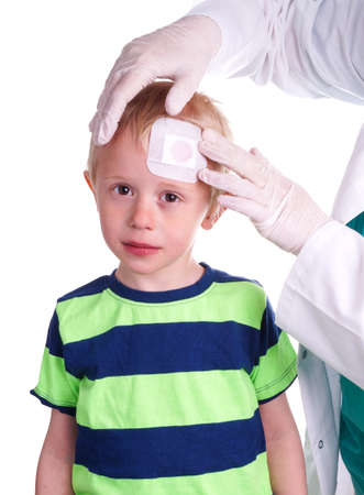 Child gets injury on the forehead and the nurse helps with getting plaster on the wound so it can heal 免版税图像 - 39589581