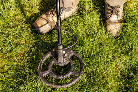 archaeologist: Metal Detector. Man with metal detector  he uses it to find archaeological treasures in the grass