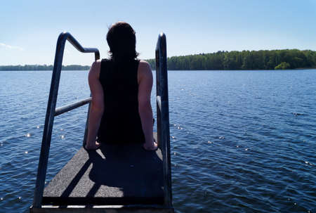 inner strength: young Woman sitting meditating on the diving board by the Lake in the Sun. She enjoys the views of the Lake