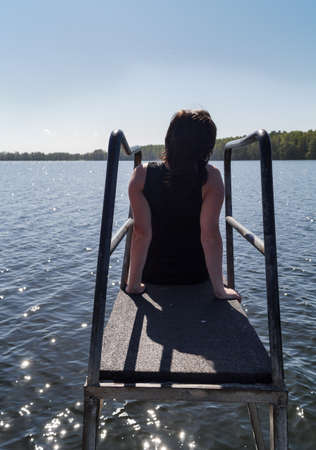 holidaying: young Woman sitting meditating on the diving board by the Lake in the Sun. She enjoys the views of the Lake