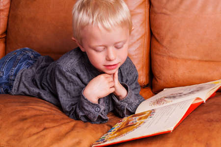 storytime: Child with Book. The Boy are lying in the Couch and is reading in his favorite Children Book