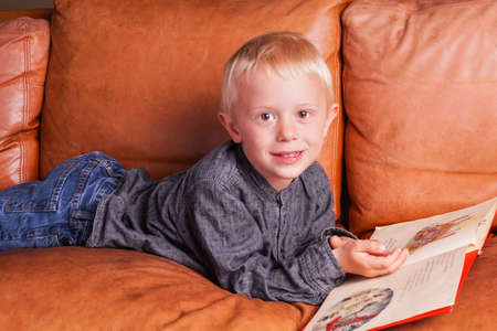 favorite book: Child with Book. The Boy are lying in the Couch and is reading in his favorite Children Book