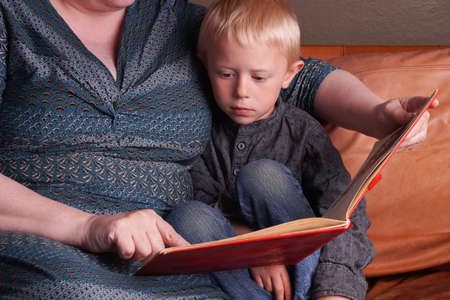 little child: Story time in the couch, Woman reads the book to the little Child Stock Photo