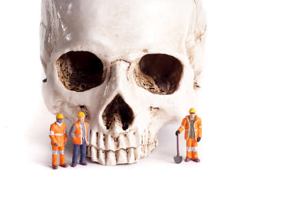 take care: Skull and small workers, work accidents , dangerous work, take care of yourself Stock Photo