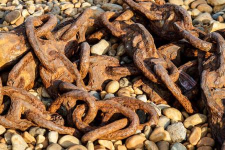 rusty chain: Old rusty ship chain lying on a rocky beach Stock Photo