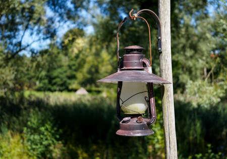 kerosene: Vintage Kerosene lamp hanging outdoors in the sun Stock Photo