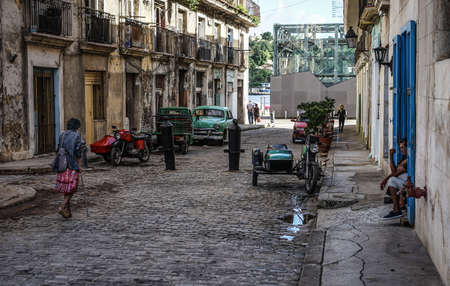Havana, Cuba - January 5, 2016: Typical scene of one of streets in the center of La Havana - colonial architecture, cars and people walking around