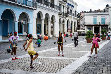 schoolgirl: Havana, Cuba - January 5, 2016: Typical scene of one of streets in the center of La Havana - A group of school children have PE lesson on one of the city square just outside their school