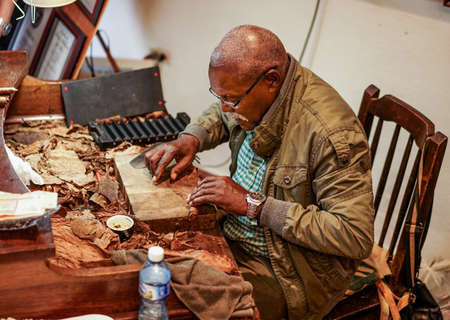 smoking a cigar: Havana, Cuba - January 8, 2016: The famous cigar-maker Jose Castelar Cairo, better known as el Cueto, about to roll a cigar