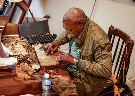 hombre fumando puro: La Habana, Cuba - 8 enero 2016: El famoso tabaquero José Castelar Cairo, más conocido como El Cueto, a punto de rodar un cigarro