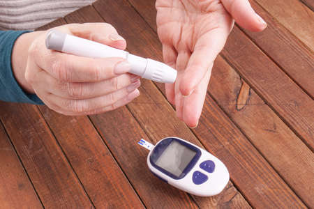hypoglycemic: a ladys hands measuring blood sugar, glucose with a home test to control her diabetes Stock Photo