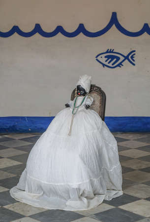 afro caribbean: Trinidad, Cuba - January 14, 2016: Afro Caribbean religion  Doll dressed in the traditional white clothes as followers of Santeria religion carrier. The doll sits in Trinidad in a residence for a Santeria priest Editorial