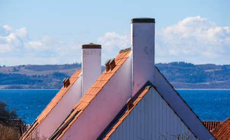 house gables: gables against the blue sea,  With white chimneys and tiled roof. sampling of typical Danish or Scandinavian building traditions