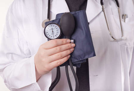diastolic: Doctor standing with blood pressure gauge, sphygmomanometer, in the hand, ready for the medical check up