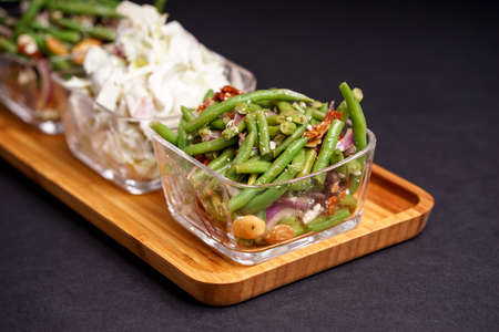 greenbeans: Healthy green beans salad and tasty Waldorf salad, served in glass bowls and bamboo tray Stock Photo