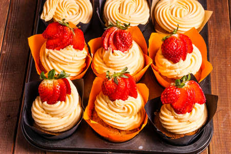frosting': Tray of Strawberry cupcakes with frosting and fresh berry