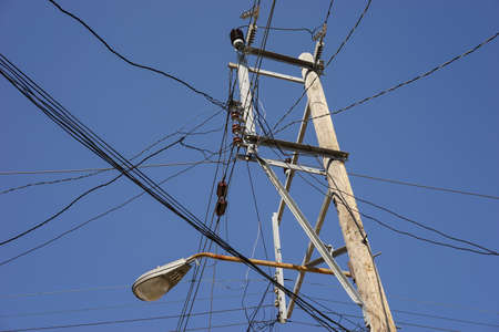 cable tangle: Old fashion power pole with many wires against the blue sky Stock Photo