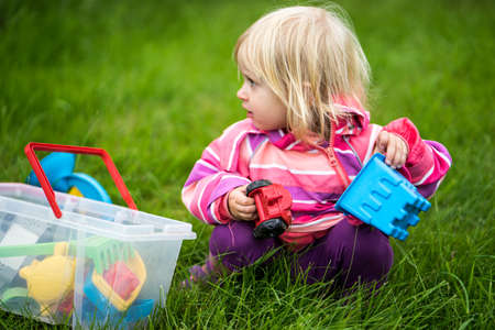 aloneness: Little girl playing with her toys in the garden