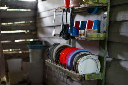 housewares: Poor kitchen in the house of worn wooden planks. The kitchen contains only the most necessary equipment like pots, plates, bowls and glasses. Wretched rickety hovel Stock Photo