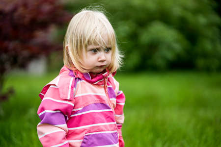 one child: Sad or bewildered girl standing alone in the garden Stock Photo