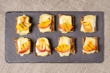 goat peach: canapes, appitizer with grilled brie and nectarine plated on a slate dish