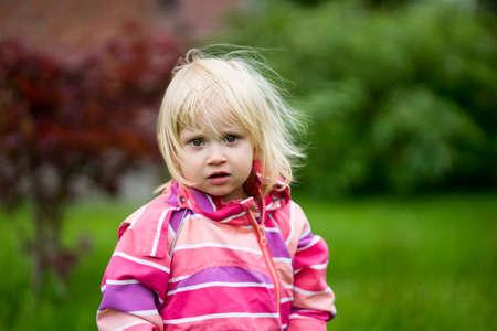 bewildered: Sad or bewildered girl standing alone in the garden Stock Photo