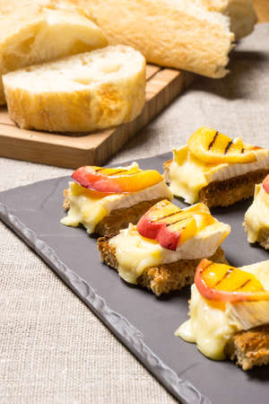 goat peach: canapes, appetizer with grilled brie and nectarine plated on a slate dish