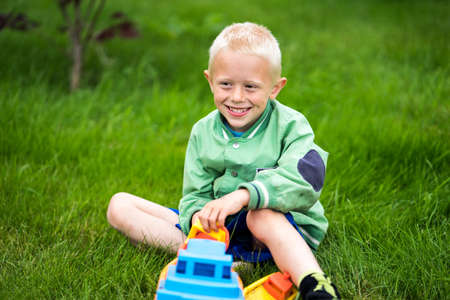 aloneness: Little boy playing with his toys in the garden