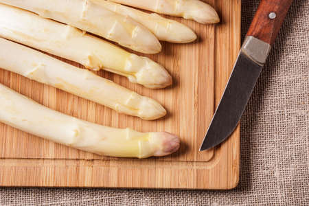 cooking implement: Delicate organic white asparagus ready to be peeled before they can be steamed Stock Photo