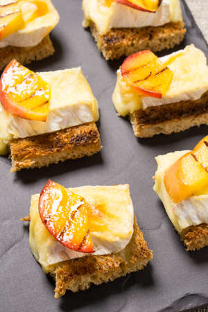 goat peach: canapes, Appetizer with grilled brie and nectarine plated on a slate dish Stock Photo