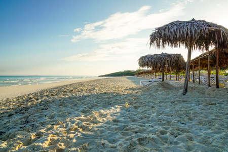 sun umbrellas: Wonderful tropical beach in Cuba, with crystal clear water, sunshine and palm leaf sun Umbrellas Stock Photo
