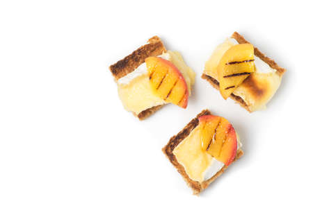 goat peach: canapes, appetizer with grilled brie and nectarine plated Isolated on white Stock Photo