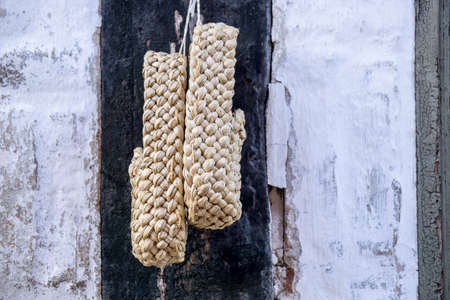 footware: a pair of plaited straw shoes hangs on the wall Stock Photo