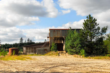 Old abandoned defaulted industrial building which stands with rusty and empty silo Stock Photo