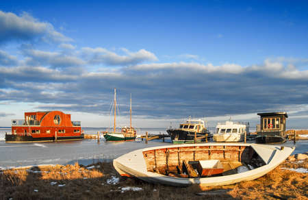 Natural Harbor with boats in the winter with frozen water Stock Photo