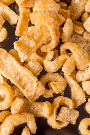 chicharon: Delicious crispy pork rinds. A crisp salty snack on black glossy background