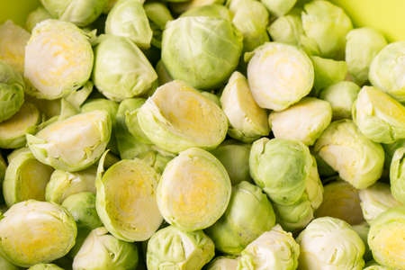 green fresh whole and cut organic Brussels sprouts, isolated on black glossy background