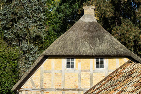 European building styles. detail of yellow timber framed house with white small windows and thatched roof Stock Photo