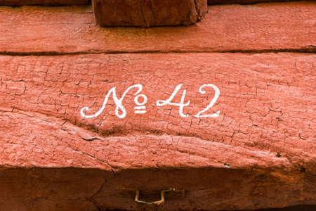 번호 42. 금이 빨간색 페인트와 흰색 고딕 숫자 42 호 작성 목조 빔