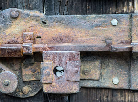 Detail of rusty iron door lock, rusty old latch lever lock, on a vintage wooden door