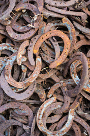 Heap of used and worn rusty Horseshoes outside blacksmith farriers shop or smithy