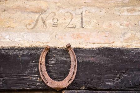 번호 아래 호스 슈와 오래 된 half-timbered 건물에 집 번호 21의 근접 촬영. 행복과 번영을 가져 오기 위해 유럽의 문틀 위에 말발굽을 놓는 것이 일반적이