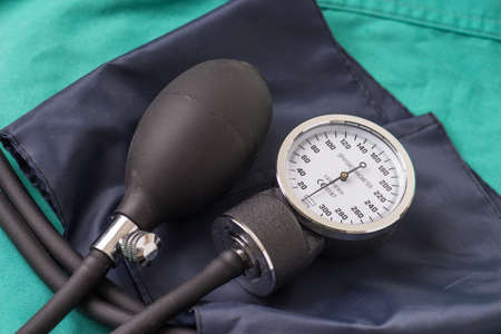 surgent: Blood pressure device located on the hospital green background. The background can be a textile part of a doctor or nurses work uniform Stock Photo