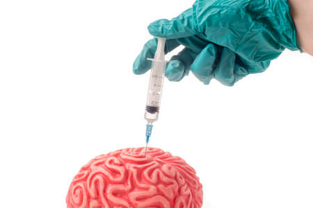 Brain injected with unknown drug. The injection is given by hand with green protective glove and is isolated on white background Standard-Bild