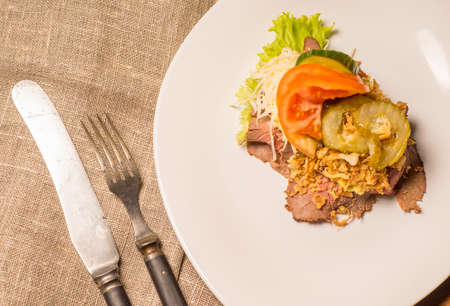 Danish specialties and national dishes, high-quality open sandwich,Roast beef with remoulade and roasted crisp onions, served on a plate ready for eating