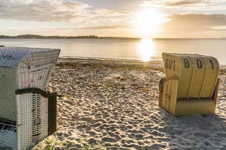 European Beach wicker chairs are placed decoratively on the beach for summer guests in the sun Stock Photo