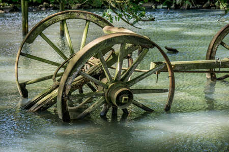 Old wooden wagon, rusty and broken, stranded in a waterhole Stock Photo