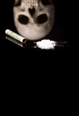 cocaine or other illegal drugs that are sniffed by means of a tube and Skull, isolated on black glossy background