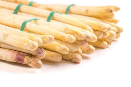 bundle of organic asparagus held together with green rubber bands isolated on white background