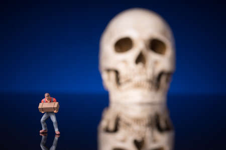 worker and blurry skull isolated om blue black background